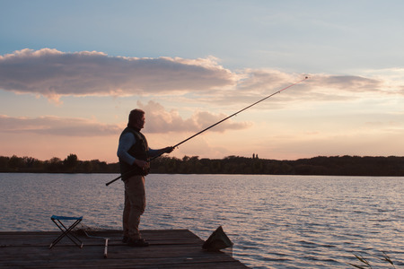 man fishing in sunset on pond photo