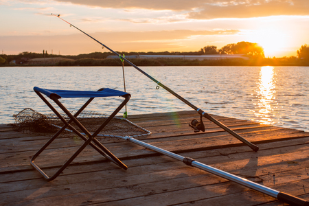 sulight: fishing utensils on a wooden platform on the pond