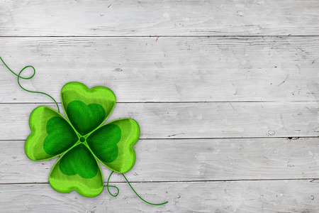 Four-leaved clover on white wooden background  Celebrating St Patricks day on March 17th  Traditional symbol of luck, happiness and wealth  Copy space  photo