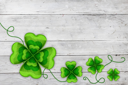 Four clovers on white wooden banner  Celebrating St Patricks day on March 17th  Traditional symbol of luck, happiness and wealth  photo