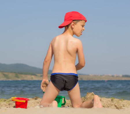6 7 year old: Astonished boy on the beach with his back staring