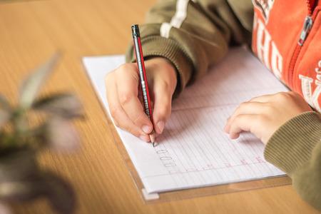 Eerste grader schrijft brieven in een notebook