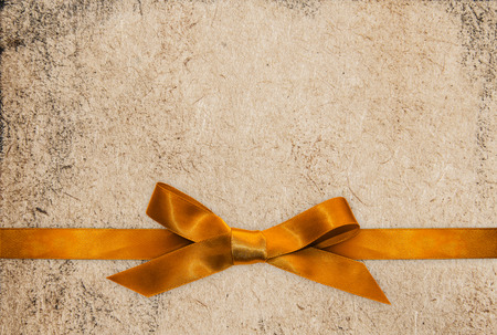 classy background: Gold ribbon bow on paper textured background