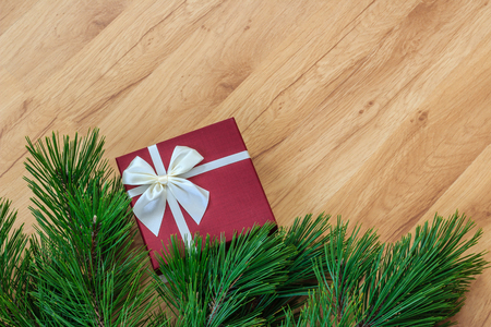 Gift box and pine branches on wooden background, bottom border, space for text