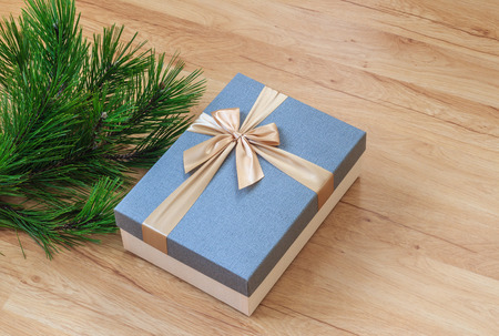 Christmas present box near pine tree branches on wooden floor