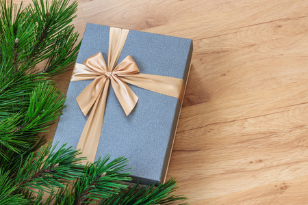 Gift box near christmas tree over wooden background