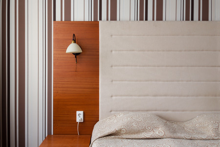 headboard: Headboard and bed in a clean hotel room Stock Photo