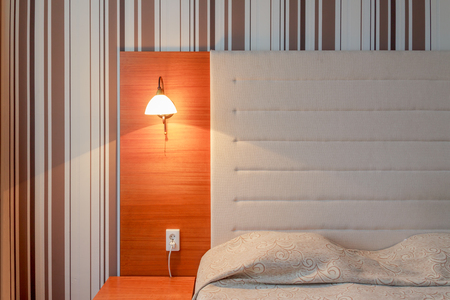 striped wallpaper: Headboards and bed in a hotel room, striped wallpaper and lighting