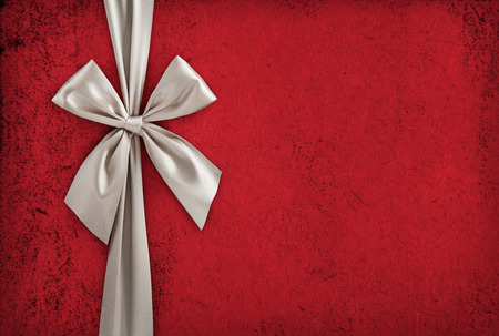 White ribbon bow over red paper, christmas backdrop, gift box background