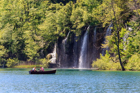 Plitvice national park in Croatia, waterfalls, couple in a boat