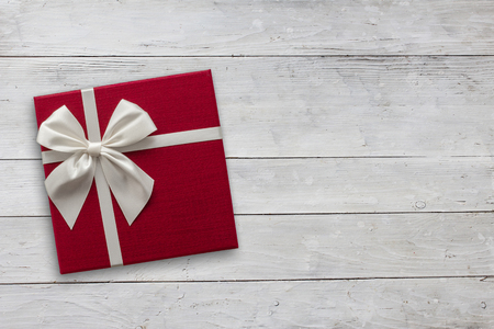 Red gift box with white ribbon over white wood, top view with copy space background