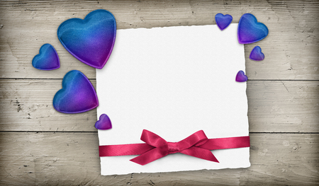 Greeting card with blue hearts and pink ribbon over wooden background
