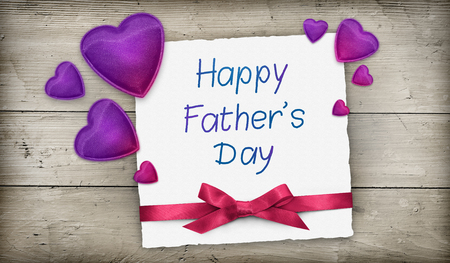 Fathers day greeting card with purple pink hearts and ribbon over wood