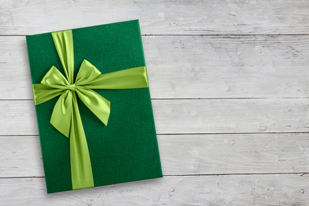 Green gift box on wood background, tip view