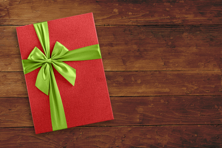 Red gift box with green ribbon on wood background view from above
