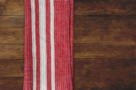Red napkin with white stripes over wooden table top view background Stock fotó