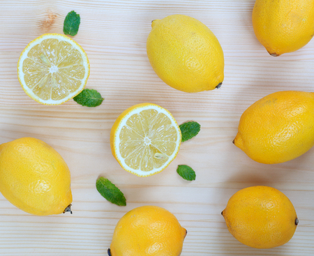 Fresh background with juicy lemons and mint leaves on light wood, top view