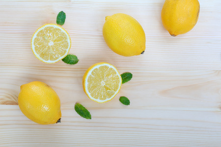 Fresh lemons and mint leaves on the table, top down view, wooden background with space for text