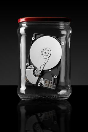 Computer hard disk in a glass jar on a black background photo