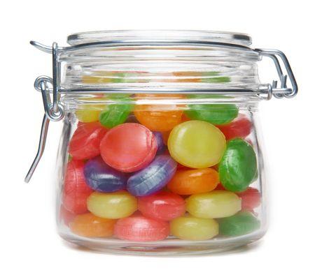 frasco: Dulces de color en una jarra de vidrio sobre un fondo blanco