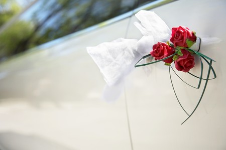 Door of white wedding car with flower and white bow photo