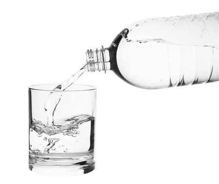 Flowing water in a glass isolated on white background