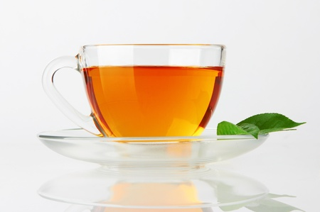 tea hot drink: Cup with tea and green leaf on white