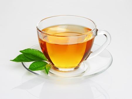 Cup with tea and green leaf on white