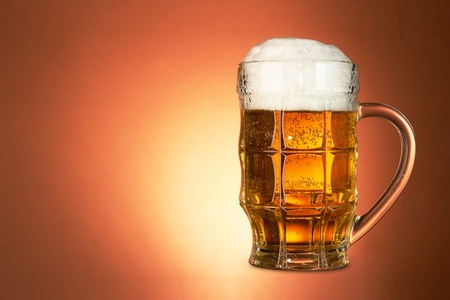 Glass of beer on brown background photo