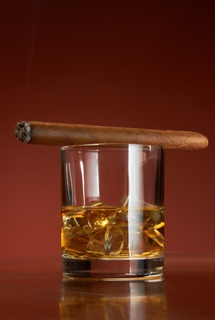Whiskey with ice cubes and cigar, on brown background photo