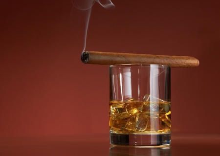 Whiskey with ice cubes and cigar, on brown background Stock Photo