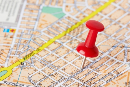 map pin: Red pushpin on a city map