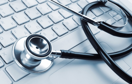 stethoscope on a white laptop computer Stock Photo