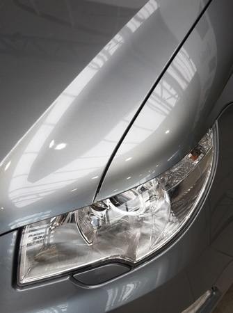 motorcar: motor-car headlight and grate of radiator on a gray car Stock Photo