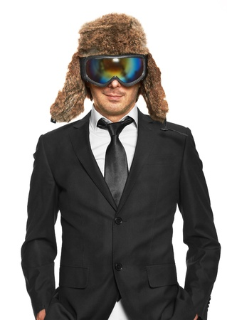 Man in ski goggles and black suit standing, isolated on white background photo