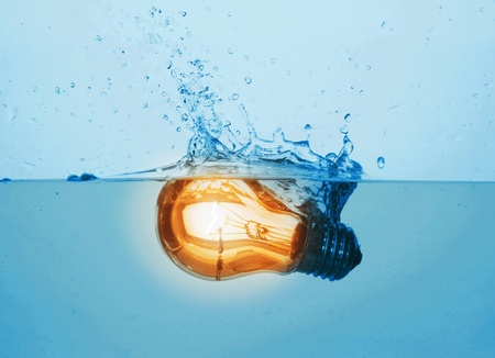 glowing yellow light bulb in water photo