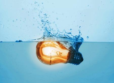 glowing yellow light bulb in water photo