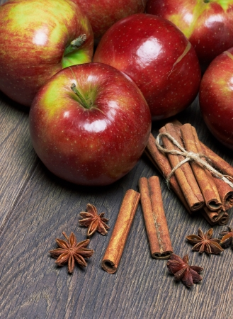 Fresh red apples with cinnamon and anise, on the wooden table Stock Photo - 19047740