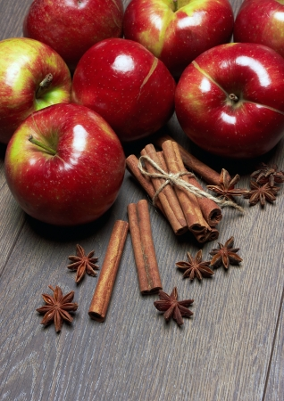 Fresh red apples with cinnamon and anise, on the wooden table photo