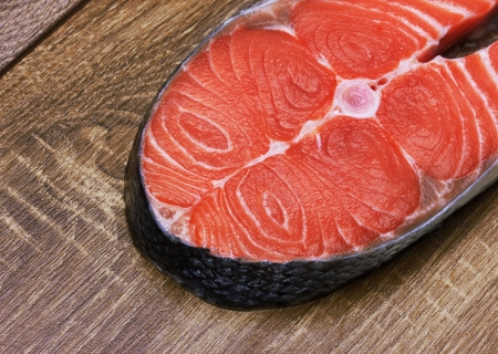 Piece of a salmon on a wood background photo