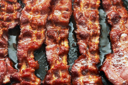 frying pan: Bacon slice being cooked in frying pan. Close up. Stock Photo