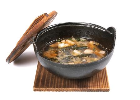 Soup on wood plank, isolated on white background photo