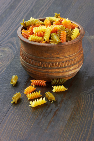 carbohydrates food: Fusilli italian pasta in wood bowl, on wood background Stock Photo
