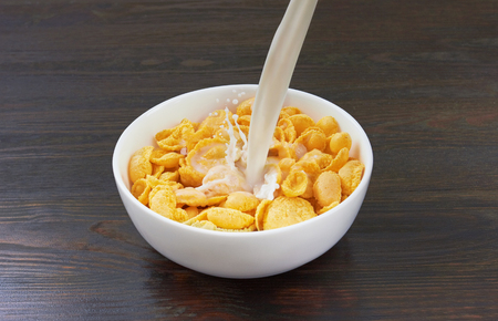 flakes: Pouring milk into corn flakes on wooden background