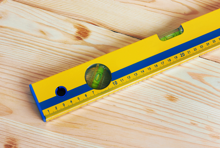 millimetre: Construction Level on wooden background
