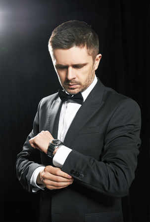 man in suite: Man in black suite whit watch, on black background