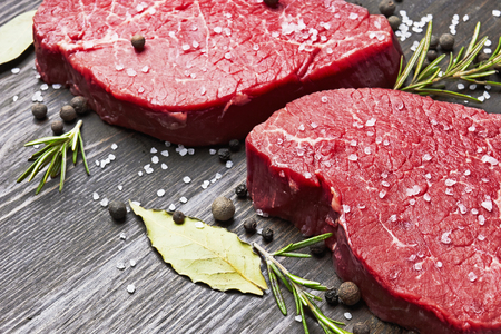 Fresh raw meat with spice on wooden background