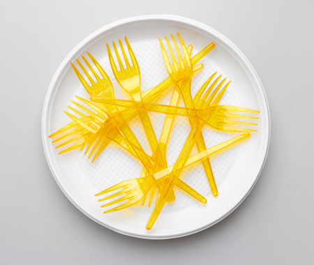 Plastic forks and plate on white background