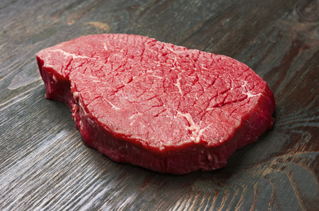 Fresh raw meat on wooden background