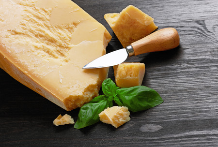 Parmesan cheese on wooden board with basil leaves